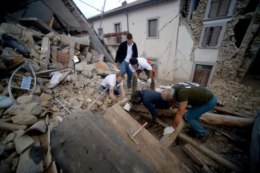 Resident search for victims in the rubble after a strong heartquake hit Amatrice on August 24, 2016. Central Italy was struck by a powerful, 6.2-magnitude earthquake in the early hours, which has killed at least three people and devastated dozens of mountain villages. Numerous buildings had collapsed in communities close to the epicenter of the quake near the town of Norcia in the region of Umbria, witnesses told Italian media, with an increase in the death toll highly likely. / AFP / FILIPPO MONTEFORTE (Photo credit should read FILIPPO MONTEFORTE/AFP/Getty Images)