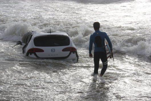 Un surfista al costat del cotxe que va ser arrossegat fins la platja de Vilassar de Mar. Imatge del 13/10/2016 en horitzontal