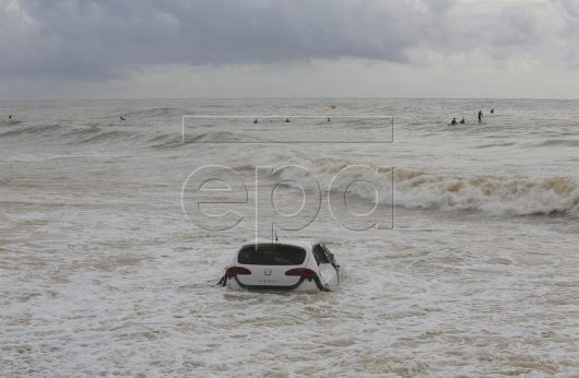 epa05583347 Waves crash against a car that was swept into the beach of Vilassar de Mar after a huge storm hit the city the previous day, in Barcelona, northeastern Spain, 13 October 2016. The storm left person dead.  EPA/ALEJANDRO GARCIA