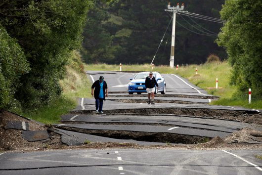 Local residents Chris and Viv Young look at damage caused by an earthquake along State Highway One near the town of Ward, south of Blenheim on New Zealand's South Island, November 14, 2016. REUTERS/Anthony Phelps