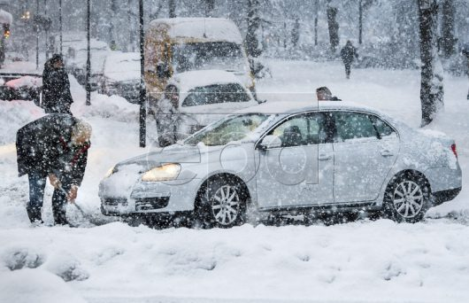 epa05624401 A man tries to get a car back on the road on the Hornsgatan Street during the heavy snowfall over Stockholm, Sweden, 09 November 2016. Traffic in the Stockholm area was hampered due to heavy snowfall. All bus traffic is halted and the main roads are blocked by trucks, buses and cars stuck in the snow. EPA/CLAUDIO BRESCIANI SWEDEN OUT